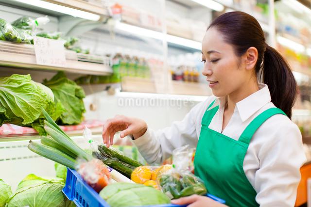 スーパーマーケットで野菜の入った箱を持つ女性店員の写真素材 [FYI01370870]