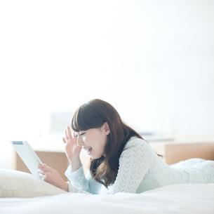 寝転んでタブレットを操作する女性の写真素材 [FYI01371284]
