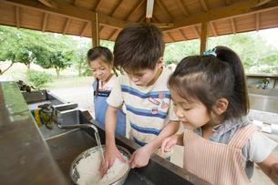 お米を研ぐ子ども達の写真素材 [FYI01371722]