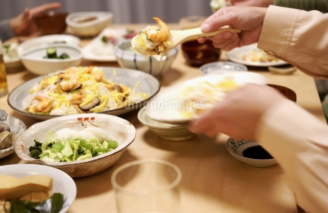 夕ご飯で五目寿司を取り分ける手の写真素材 [FYI01371741]