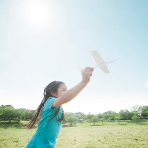 飛行機を持って走る女の子の写真素材 [FYI01372063]