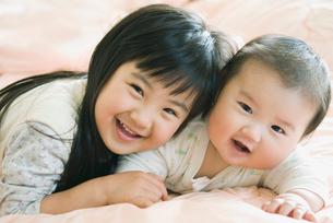 寝転ぶ笑顔の姉弟の写真素材 [FYI01372528]