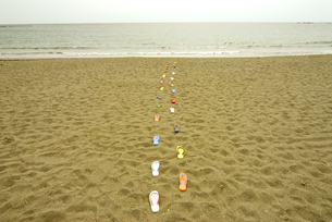 砂浜を歩くビーチサンダルの列の写真素材 [FYI01372811]