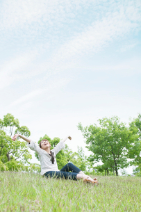 草原に座って伸びをする女性の写真素材 [FYI01372814]