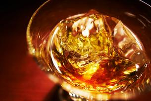 琥珀色に輝くグラスに入ったロックのウィスキーの写真素材 [FYI01373817]