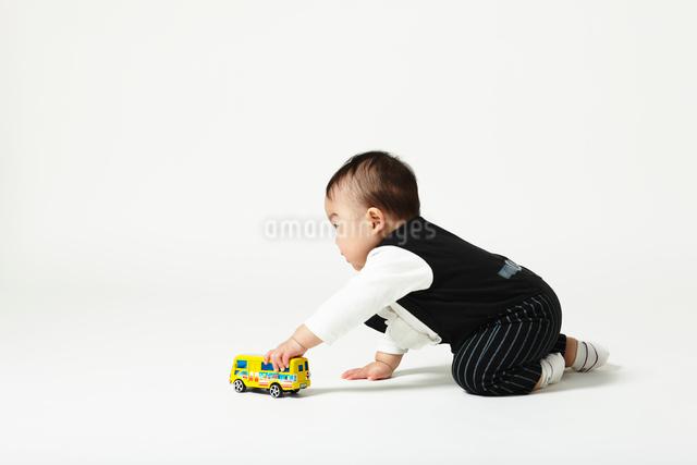 バスのおもちゃで座って遊ぶ蝶ネクタイの正装した赤ちゃんの写真素材 [FYI01373845]