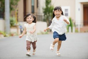 笑顔で走る姉妹の写真素材 [FYI01373862]