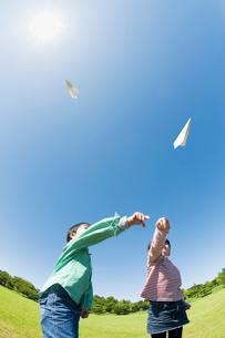 紙飛行機を飛ばす2人の子供達の写真素材 [FYI01374325]