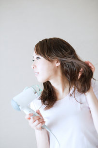 髪の毛を乾かす女性の写真素材 [FYI01375049]