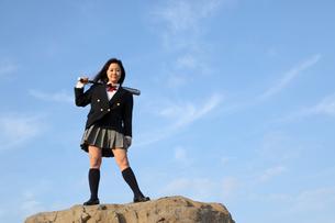 岩の上でバットを持ちポーズをとる女子高生の写真素材 [FYI01375328]