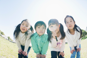虫眼鏡をのぞく子供達の写真素材 [FYI01375951]
