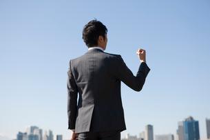 ビジネススーツを着てガッツポーズをしている男性の後姿の写真素材 [FYI01376489]