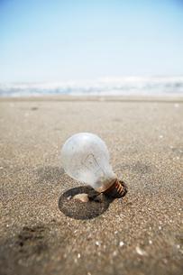 砂浜に置かれた壊れた電球の写真素材 [FYI01376638]
