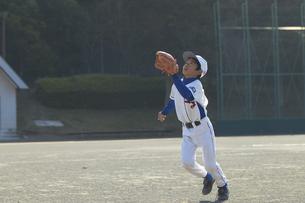 ボールをキャッチしようとする少年の写真素材 [FYI01376872]