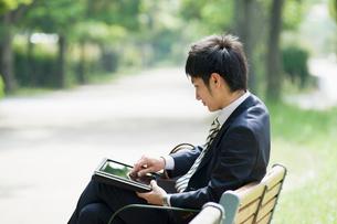 タブレットを操作するビジネスマンの写真素材 [FYI01376942]