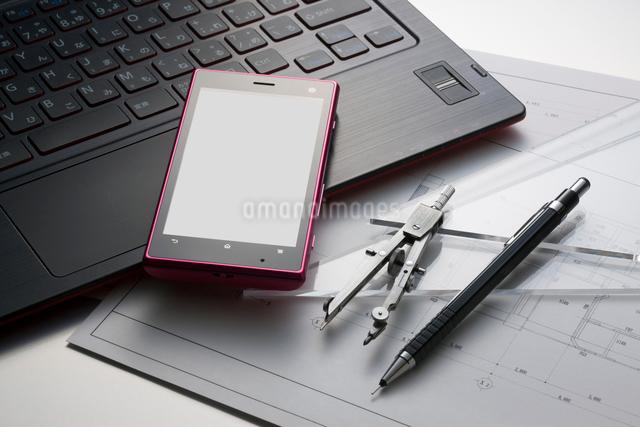スマートフォンと図面の上のコンパスと三角定規の写真素材 [FYI01377025]