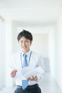 ファイルを持って微笑むビジネスマンの写真素材 [FYI01377653]