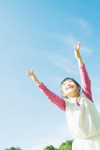 青空に向かって両手をあげる女の子の写真素材 [FYI01377818]
