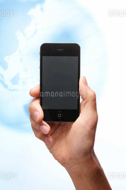 地球儀を背景に黒いスマートフォンを持つ手の写真素材 [FYI01378035]