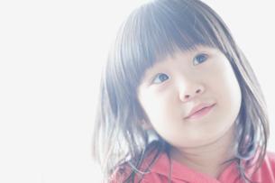 首を傾げて見上げる女の子の写真素材 [FYI01379157]