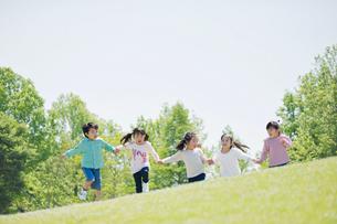 手をつないで走る5人の子供達の写真素材 [FYI01379885]