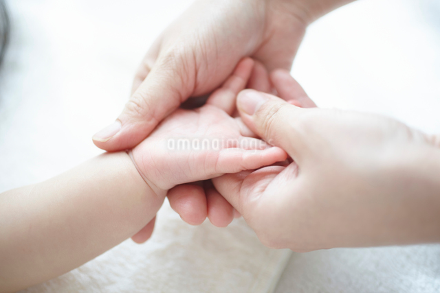 お母さんに手のベビーマッサージをしてもらう気持ち良い赤ちゃんの写真素材 [FYI01380167]