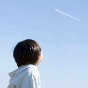 飛行機雲を見上げる男の子の後姿の写真素材 [FYI01381115]