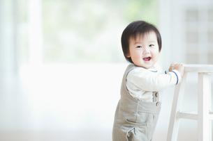 椅子につかまって笑う赤ちゃんの写真素材 [FYI01381973]
