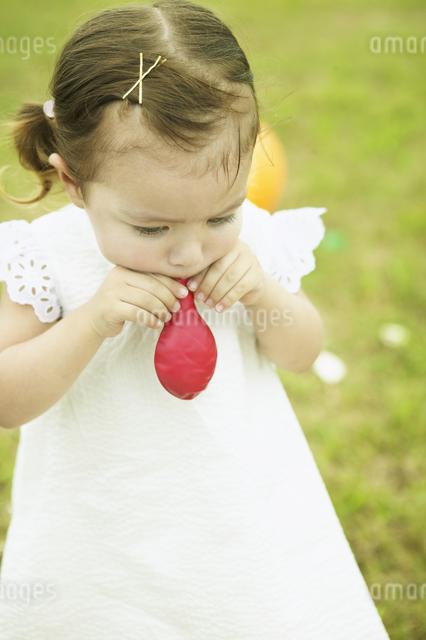 風船を膨らます幼い少女の写真素材 [FYI01384491]