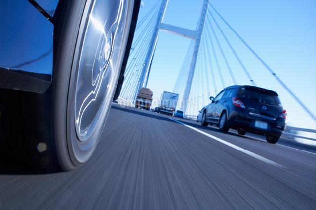 道路を走る車のタイヤと地面の写真素材 [FYI01385713]
