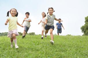 丘を走ってくる子ども達の写真素材 [FYI01385750]