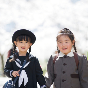 桜並木で笑う2人の幼稚園児の女の子の写真素材 [FYI01385824]