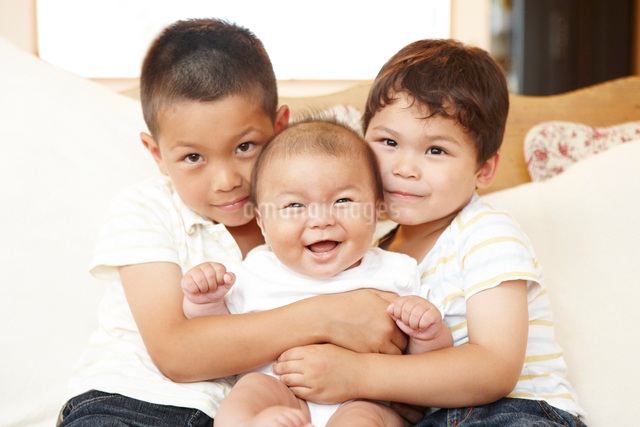 笑顔の赤ちゃんを抱く兄弟の写真素材 [FYI01386346]