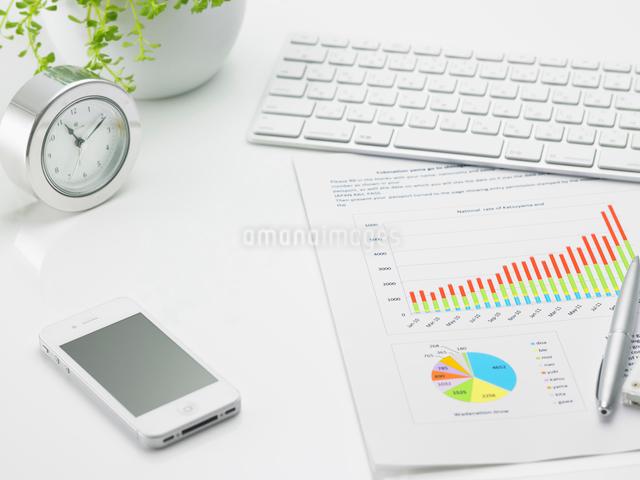 キーボードとスマートフォンとグラフ資料が乗ったビジネスデスクの写真素材 [FYI01386625]