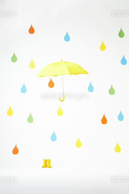 カラフルな雨のしずくバックと宙に浮く黄色い傘の写真素材 [FYI01387216]