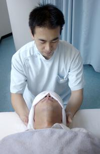 日本人男性を指圧する男性指圧師の写真素材 [FYI01387439]