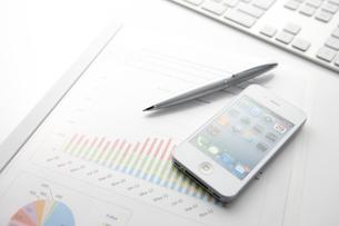 キーボードとスマートフォンとグラフ資料が乗ったビジネスデスクの写真素材 [FYI01388284]