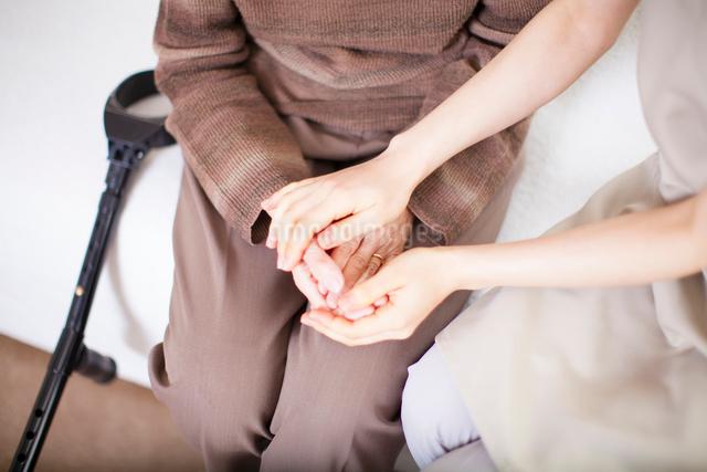 おばあちゃんと手を重ね合わせる介護士さんの写真素材 [FYI01388494]
