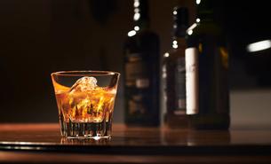 ボトルが並ぶカウンターに輝くグラスに入ったロックのウィスキーの写真素材 [FYI01389167]