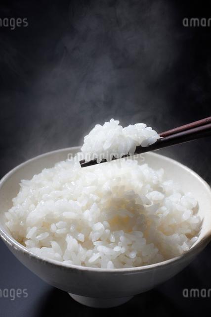 白いお茶碗に盛られた湯気のたつ美味しそうなご飯とお箸の写真素材 [FYI01389309]