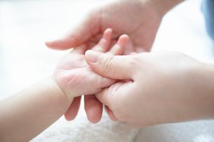 お母さんに手のベビーマッサージをしてもらう気持ち良い赤ちゃんの写真素材 [FYI01389317]