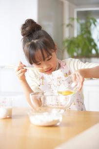 台所でパン作りをするボールの卵を混ぜる女の子の姉妹の写真素材 [FYI01389318]