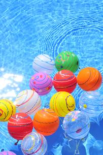 水に浮くカラフルなヨーヨーの写真素材 [FYI01389744]