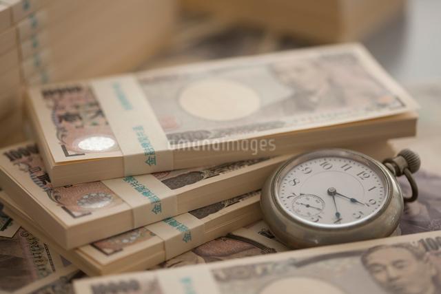 一万円札の札束と懐中時計の写真素材 [FYI01390328]