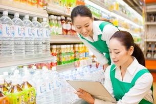 スーパーマーケットで商品在庫管理をする女性従業員の写真素材 [FYI01392822]