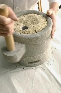 石臼でそば粉をひく手の写真素材 [FYI01394223]