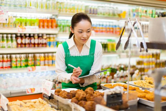 スーパーマーケットの商品在庫管理をする女性従業員の写真素材 [FYI01394306]