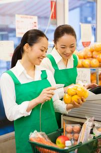 スーパーマーケットのレジに立つ女性店員の写真素材 [FYI01394380]