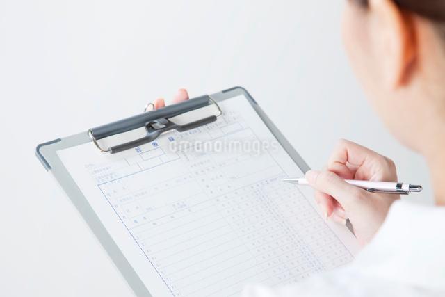 診療録を持つ看護師の斜め後ろよりの写真素材 [FYI01394677]