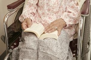車椅子の日本人老人女性患者の本を開く手元の写真素材 [FYI01395676]